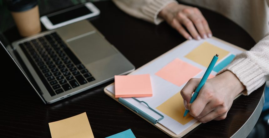 Closeup shot of student hand holding pen and writing information on sticky note, exam preparation, learning language. Woman freelancer working from home, using scrum for productivity